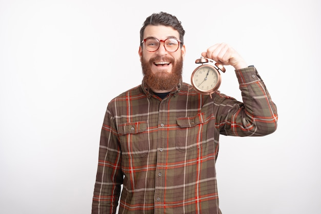 Happy bearded man wearing glasses is smiling at the camera and holding an alarm clock on white space.
