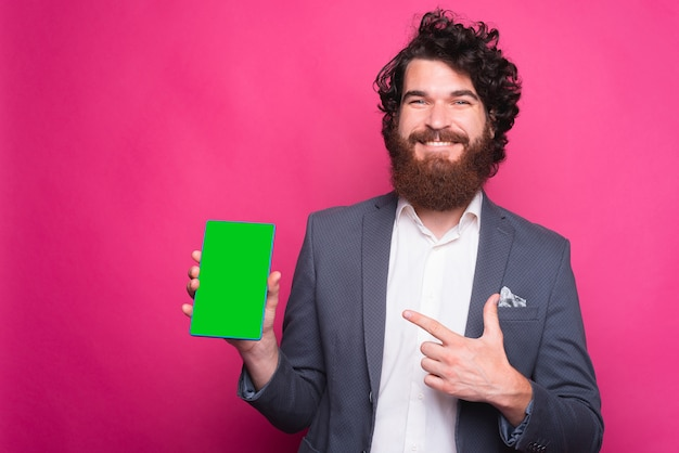 スーツを着て、ピンクの背景の近くのタブレットの緑色の画面を指して幸せなひげを生やした男