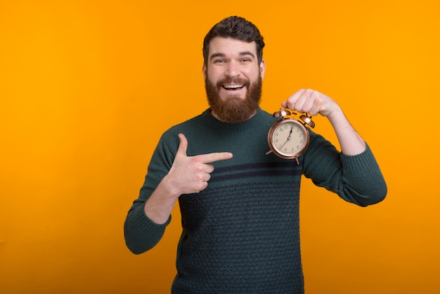 Happy bearded man wearing sweater is holding an alarm clock on yellow space while smiling at the camera. it's time.