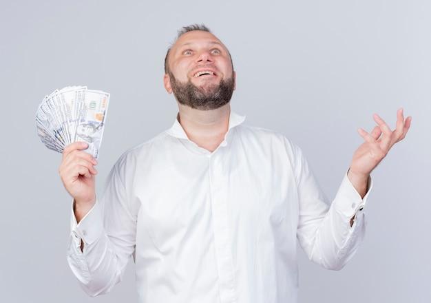 흰 벽 위에 서있는 기쁨을 찾는 현금을 들고 흰 셔츠를 입고 행복한 수염 난 남자