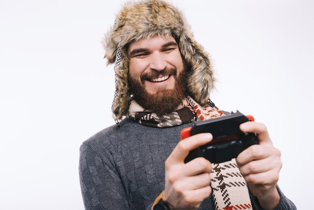 Happy bearded man wearing a winter fur cap hat, a scarf and a sweater playing with a joystick, smiling and being happy.