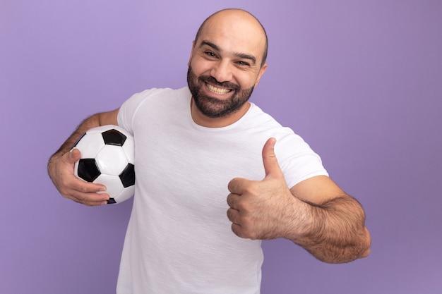 Uomo barbuto felice in maglietta bianca che tiene il pallone da calcio che sorride allegramente mostrando i pollici in su in piedi sopra la parete viola