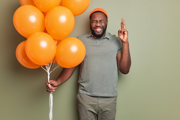 Happy bearded man with beard crosses fingers makes wish on birthday holds bunch of bright orange inflated balloons dressed in stylish clothing stands indoor