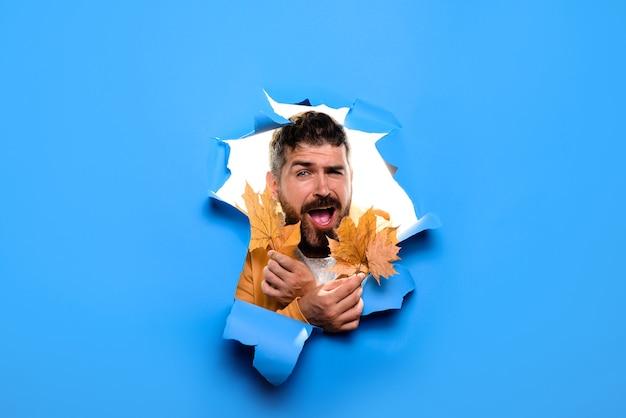 Happy bearded man with golden leaf autumnal mood autumn sales smiling man look through torn paper