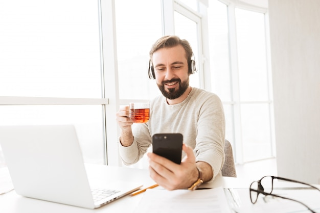 Happy bearded man  with short brown hair drinking tea and listening to music via headphones, while taking selfie on cell phone