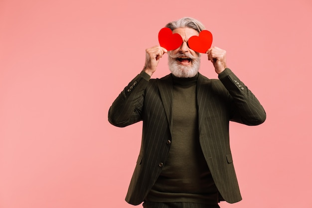 Happy bearded and mustache mature man in khaki suit holding two red hearts near eyes greeting valentine isoleted pink background.