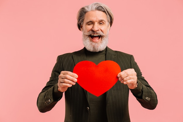 Happy bearded and mustache mature man in khaki suit with red heart greeting valentine isoleted pink background.