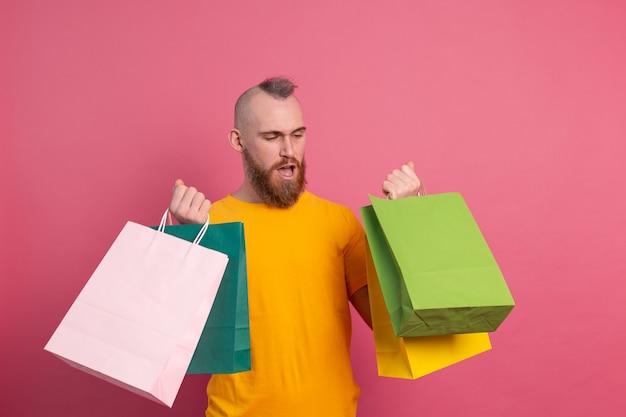 다채로운 쇼핑백 스튜디오 분홍색 배경으로 행복 수염 된 긍정적 인 남자 캐주얼 모습