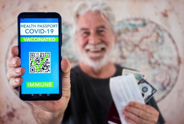 수염을 기른 행복한 노인이 코로나바이러스 백신 접종을 받은 사람들을 위한 디지털 건강 여권 앱을 보여줍니다