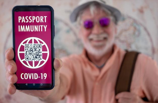 수염을 기른 행복한 노인은 다시 여행할 준비가 된 코로나바이러스 예방접종을 받은 사람들을 위한 건강 여권 앱을 보여줍니다