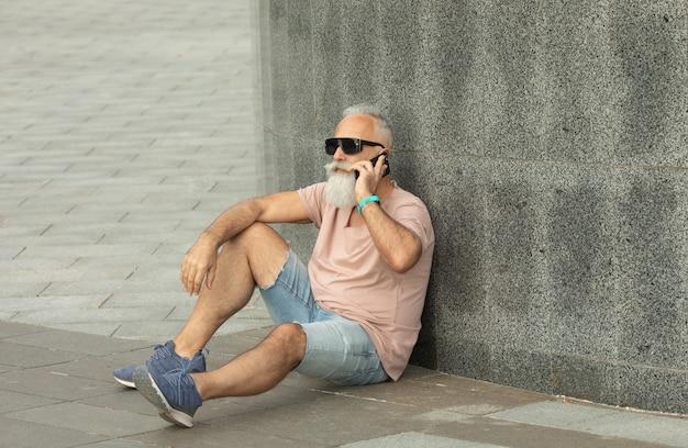 電話で話している幸せなひげを生やした年配の男性。スマートフォンで話している陽気なトレンディな成熟した男。屋外で電話で話す現代の年配の男性の肖像画。
