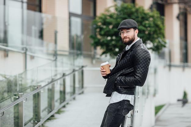 Felice uomo barbuto, serio ed elegante che cammina per le strade della città vicino al moderno centro uffici con caffè