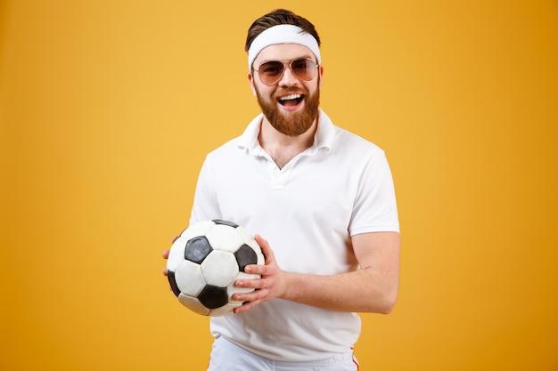Счастливый бородатый спортсмен держит футбольный мяч