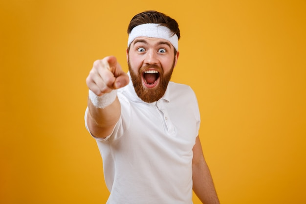 Счастливый бородатый спортсмен, указывая на камеру