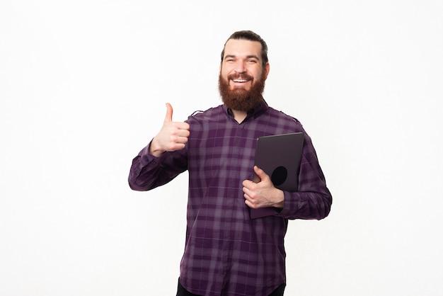 親指を立ててラップトップを持って幸せなひげを生やした学生男