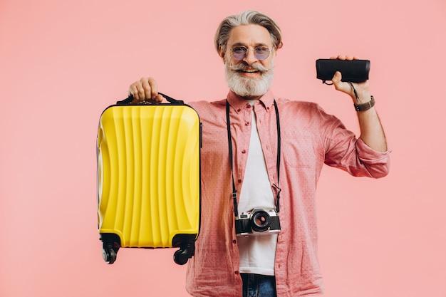 スーツケースとポータブルスピーカーを保持しているカメラでサングラスで幸せなひげを生やしたスタイリッシュな男