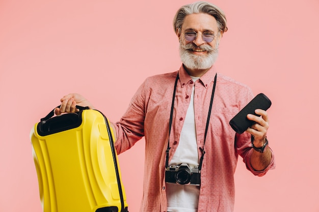 Happy bearded stylish man in sunglasses with camera holding a suitcase and a portable speaker