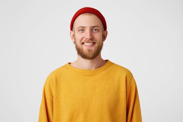 Счастливый бородатый молодой человек, смотрит с радостным выражением лица, дружелюбно улыбается, носит желтый свитер и красную шляпу