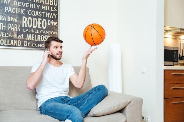 バスケットボールのボールで遊んで、自宅のソファで携帯電話で話している幸せなひげを生やした若い男