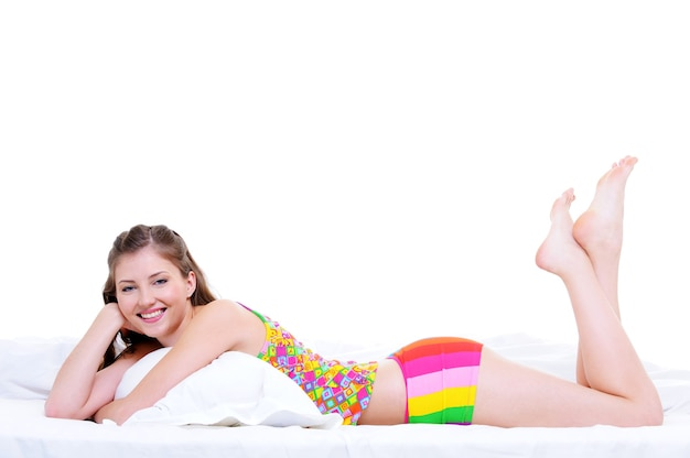 ベッドで横になっている幸せな美しい若い女性