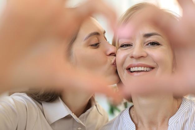 幸せな美しい大人の女性と彼女の娘は、抱きしめ、笑顔で両手で心を形成します。母の日。愛、家族の概念。