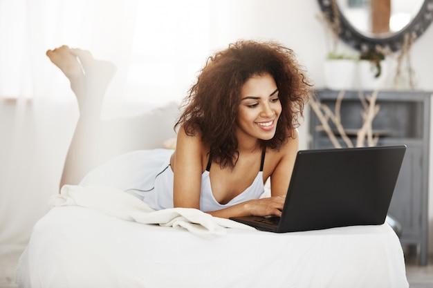 Счастливая красивая африканская женщина в пижаме лежа на кровати дома усмехаясь смотрящ компьтер-книжку.