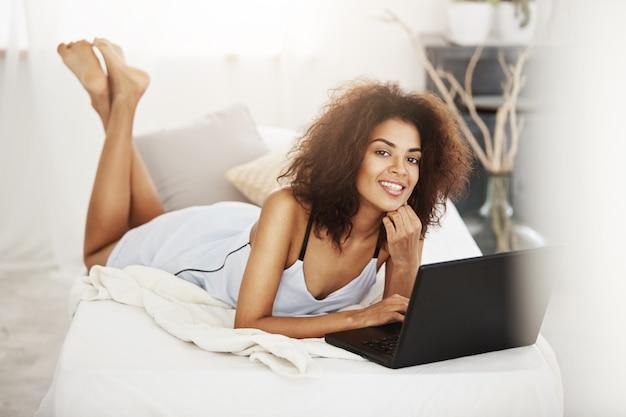 Счастливый красивая африканская женщина в пижамы, лежа с ноутбуком на кровати у себя дома улыбается.