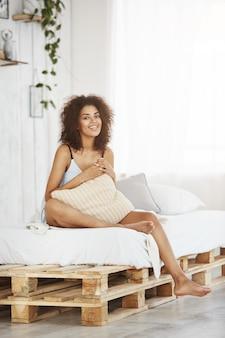 Счастливая красивая африканская женщина в пижаме усмехаясь держащ подушку сидя на кровати дома в ее квартире просторной квартиры.