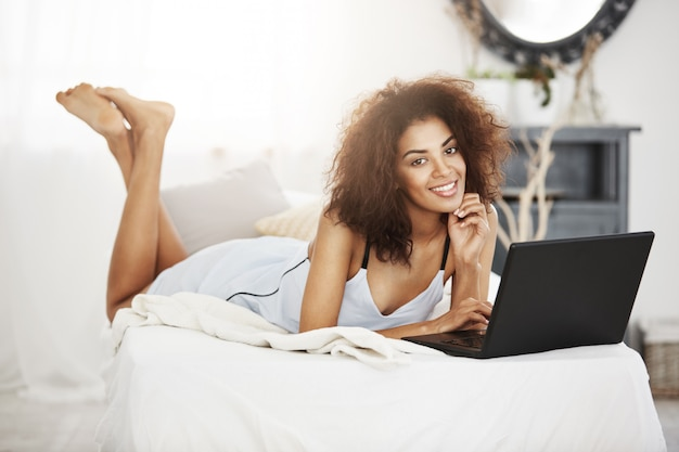 Happy beautiful african woman in sleepwear lying with laptop on bed at home smiling.