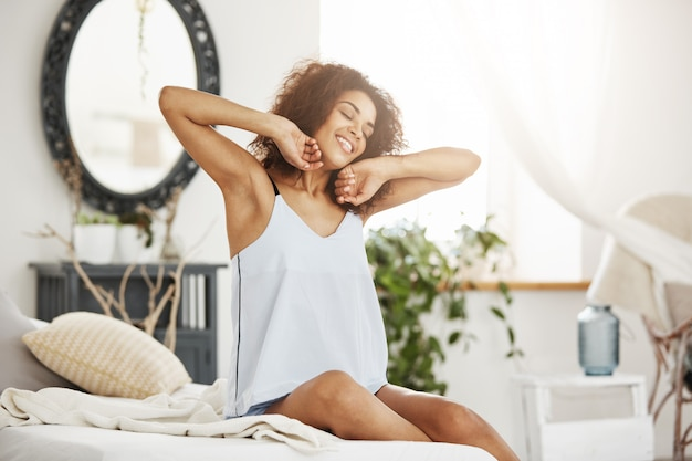 Happy beautiful african woman in sleepwear stretching smiling with closed eyes sitting on bed at home woke up in the morning on a sunny day.