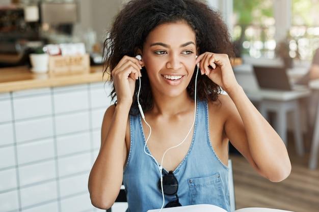 カフェで休んで座っているヘッドフォンを入れて笑って幸せなアフリカ美女。