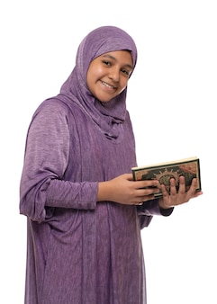 Happy beautiful arab muslim girl in islamic fashion dress holding holy book of quran, isolated on white background