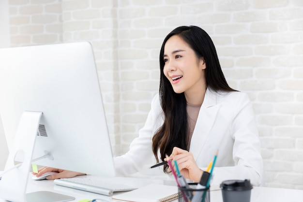 Happy beautiful asian businesswoman working on computer in the office