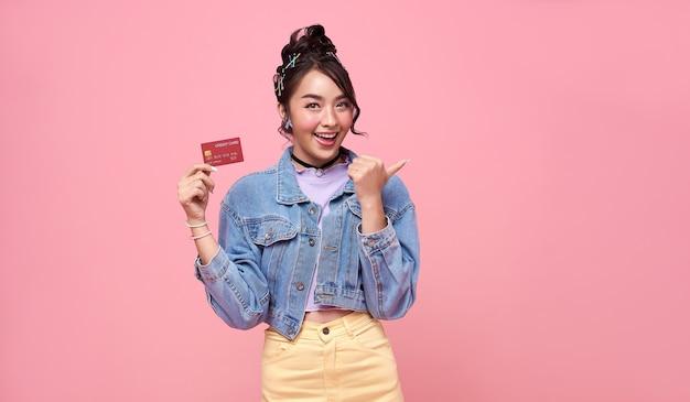 ピンクの背景で隔離の手でクレジットカードを示す幸せな美しいアジアの買い物中毒の10代の女性。