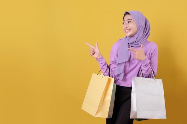 행복 한 아름 다운 아시아 쇼핑 중독 여성과 신용 카드 쇼핑 가방을 들고 명랑 하 고 즐거운 뭔가를 가리키는