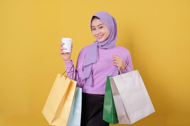 행복 한 아름 다운 아시아 쇼핑 중독 여성 음료 한 잔을 가져와 쇼핑백을 들고