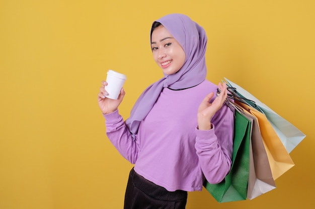 Happy beautiful asian shopaholic women bring a glass of drink and holding shopping bags, smile and cheerful