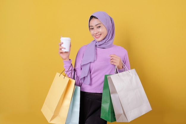 Happy beautiful asian shopaholic women bring a glass of drink and holding shopping bags