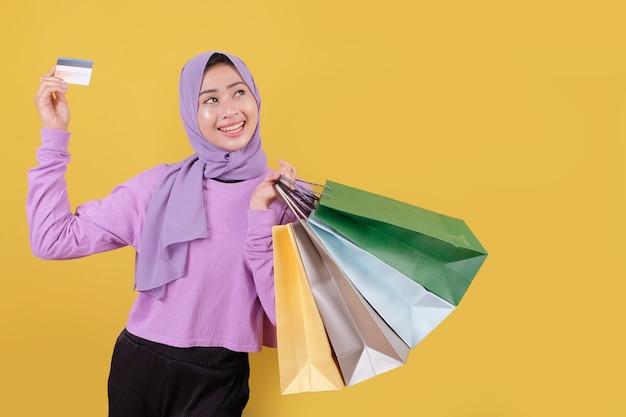 명랑하고 즐거운 쇼핑 가방을 들고 행복 아름다운 아시아 쇼핑 중독 여성