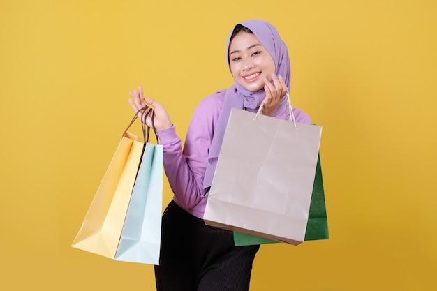 쾌활 한 쇼핑백을 들고 행복 한 아름 다운 아시아 쇼핑 중독 여성