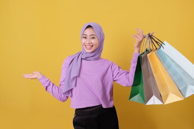 Happy beautiful asian shopaholic women holding and showing shopping bags cheerful
