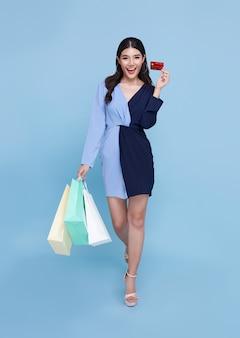 青いドレスと青い背景で隔離の買い物袋を保持しているクレジットカードを身に着けている幸せな美しいアジアの買い物中毒の女性。