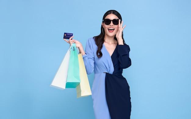青いドレスと青で隔離の買い物袋を保持しているクレジットカードを身に着けている幸せな美しいアジアの買い物中毒の女性。