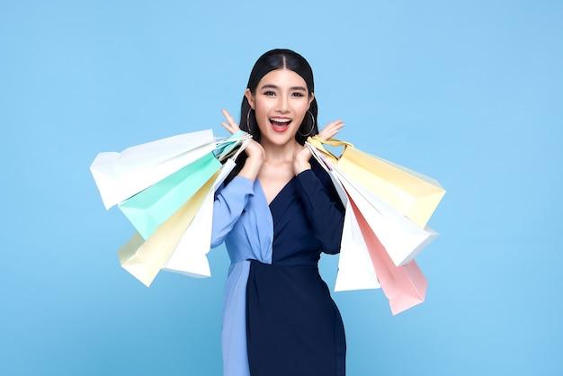 青いドレスを着て、青い背景で隔離の買い物袋を保持している幸せな美しいアジアの買い物中毒の女性。