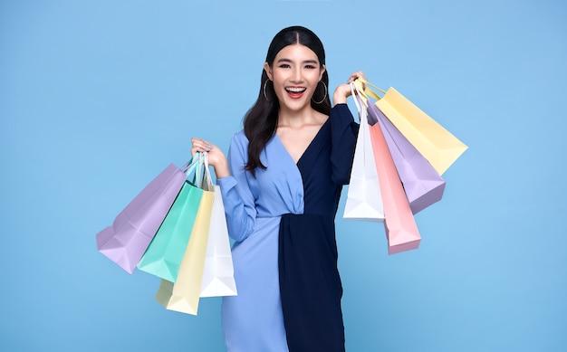 青いドレスを着て、青で隔離の買い物袋を保持している幸せな美しいアジアの買い物中毒の女性。
