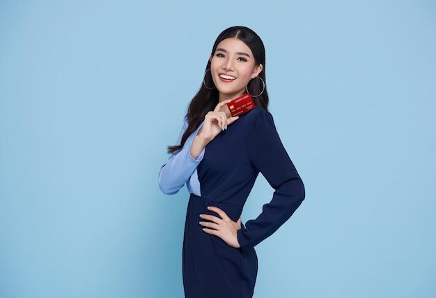 青い背景に分離された手にクレジットカードを示す青いドレスを着て幸せな美しいアジアの買い物中毒の女性。