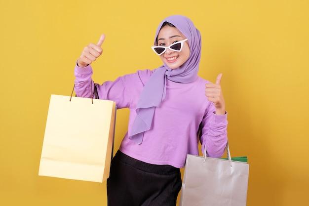쇼핑 가방을 들고 안경과 신용 카드를 입고 행복 아름다운 아시아 쇼핑 중독 여성