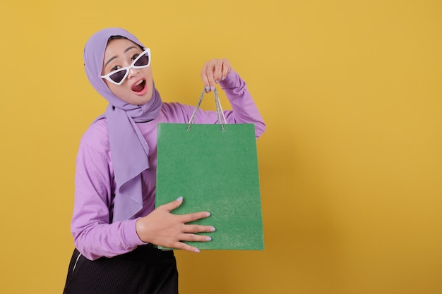 Happy beautiful asian shopaholic women wearing glasses and credit card holding shopping bags