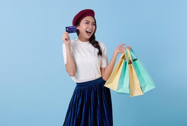 青い背景で隔離のクレジットカードと買い物袋を保持している幸せな美しいアジアの10代買い物中毒の女性。