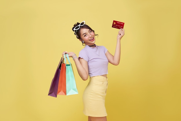 黄色の壁に隔離のクレジットカードと買い物袋を保持している幸せな美しいアジアの10代買い物中毒の女性。